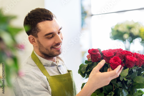 Leinwanddruck Bild small business, sale and floristry concept - florist or seller setting red roses at flower shop