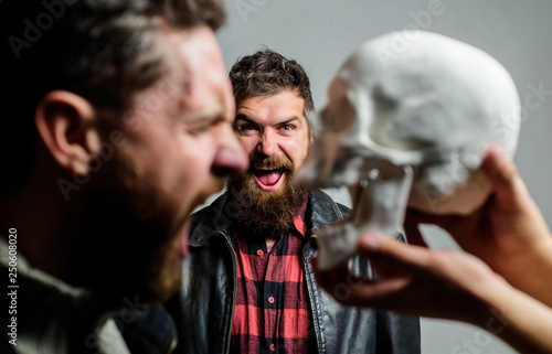 Human fears and courage. Looking deep into eyes of your fear. Man brutal bearded hipster looking at skull symbol of death. Overcome your fears. Be brave. Focused on breaking fear. Psychology concept