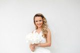 Blonde bride posing with bouquet of flowers