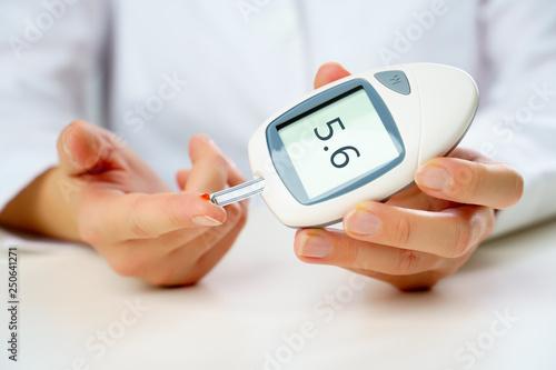Leinwanddruck Bild Photo of patient's hand with glucometer.