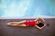 Young woman in bikini posing by the swimming pool outdoor