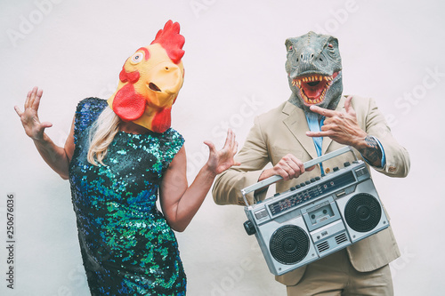 Crazy senior couple wearing chicken and t-rex mask while dancing outdoor - Mature trendy people having fun celebrating and listening music with boombox - Absurd concept of masquerade funny holidays - 250676036