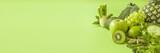 Green health smoothie fruits and vegetables, kale leaves, lime, apple, kiwi, grapes, banana, avocado, lettuce pineapple salat. Copy space. Raw, vegan, vegetarian, alkaline food concept.