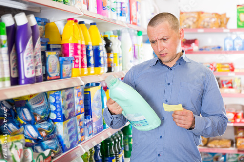 Man buying household chemicals on shopping list