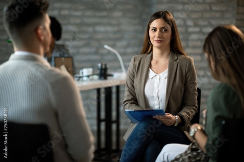 Young insurance agent having a meeting with a couple in the office.