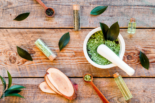 Make cosmetics with tea tree essential oil. Homemade cosmetics. Fresh tea tree leaves, mortar and pestel, cosmetics on rustic wooden background top view pattern - 250772672