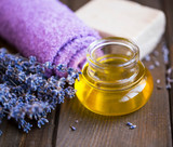 Lavender spa oil setting, spa and massage oil still life, lavender towel, flowers , natural soap and lavender oil on wooden background