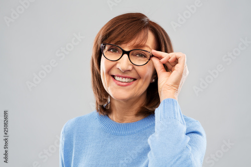 vision and old people concept - portrait of smiling senior woman in glasses over grey background © Syda Productions