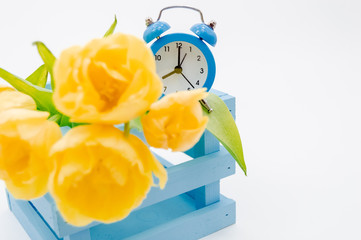 Womans holiday yellow Spring tulips with an alarm clock and blue wooden cart box isolated on white background.Several objects Top horizontal view copyspace