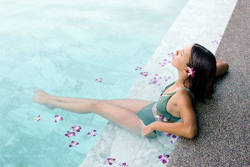 Girl relaxing in tropical spa pool with flowers © Alena Ozerova