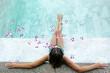 Leinwanddruck Bild - Girl relaxing in tropical spa pool with flowers