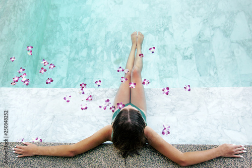Leinwanddruck Bild Girl relaxing in tropical spa pool with flowers