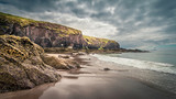 Beach with big rocks in the foreground and cliffs in the background under a dark clouded sky in Ireland