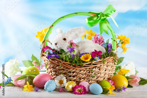 Easter composition with bunny in basket, spring flowers and colorful Easter eggs . © sarsmis