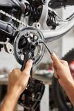 Cropped shot of serviceman working in bicycle repair shop, professional mechanic repairing bike using special tool