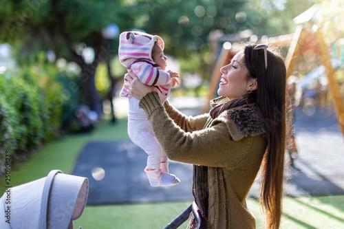 canvas print picture Junge, glückliche Mutter spielt mit ihrem Baby auf dem Spielpatz im Park