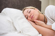 Young woman sleeping lying on a white bed in the morning