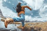 Man hiker jumps across water in mountain area