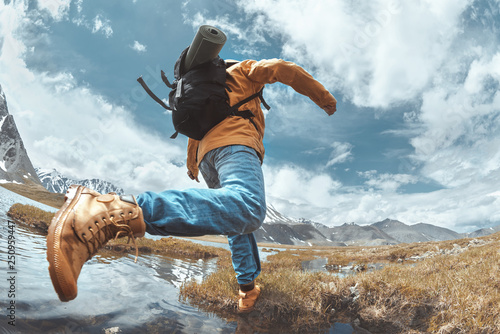Leinwanddruck Bild Man hiker jumps across water in mountain area