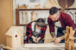 Leinwandbild Motiv Young caucasian father and his pre-teen son working together in a wooden workshop, building a wooden bird house. Little boy dressed in apron and wearing protective glasses working with a hummer