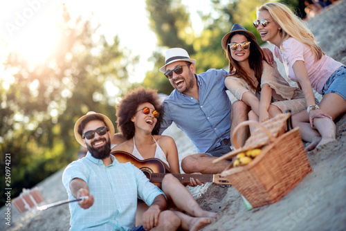 Happy group of friends taking a picture on the beach