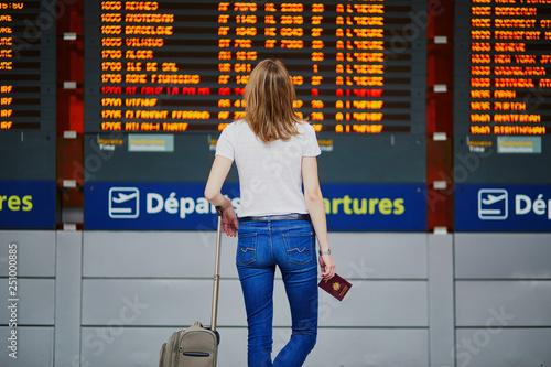 Leinwanddruck Bild Young woman in international airport