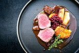 Traditional saddle of venison with fried mashed potatoes and fruits in game red wine sauce as top view on a modern design plate with copy space