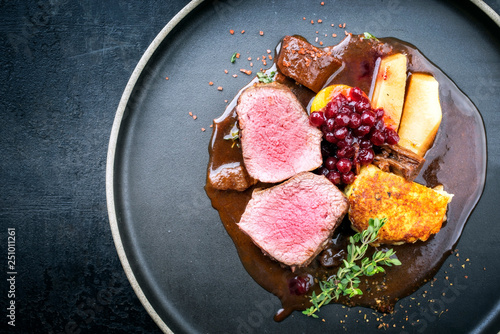 Leinwanddruck Bild Traditional saddle of venison with fried mashed potatoes and fruits in game red wine sauce as top view on a modern design plate with copy space