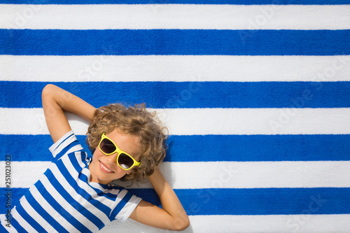 obraz PCV Top view portrait of child on striped beach towel