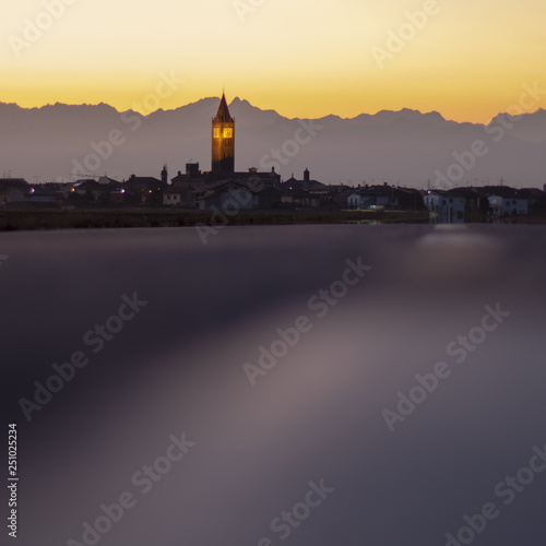 Antico borgo italiano al tramonto con le Alpi come sfondo