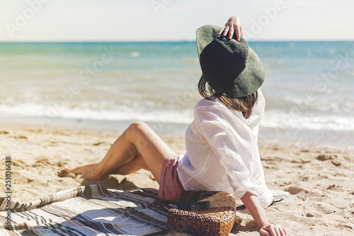 Leinwandbild Motiv Summer vacation concept. Happy young woman relaxing on beach. Hipster slim girl in white shirt and hat sitting and tanning on beach near sea with waves, sunny warm weather. Peaceful calm moment