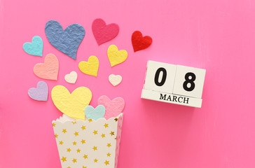 wooden March 8 calendar next to paper colorful hearts over pink wooden background © tomertu