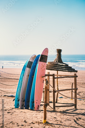 Leinwandbild Motiv Different colors of surf on a the sandy beach in Casablanca - Morocco. Beautiful view on sandy beach and ocean. Surf boards for renting. Surfer school.