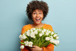 Happy African American woman with curly hair expresses true positive emotions, has cheerful mood, looks upwards, carries spring white flowers, wears orange jumper, isolated over blue studio wall