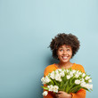 Vertical photo of joyful woman gazes upwards, smiles broadly, holds white tulips, wears jumper, rejoices Women Day, isolated over blue background with empty space above. Blossom, spring, good mood