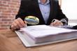 Businessman Examining Invoice Through Magnifying Glass