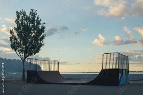 skateboarder rides on a ramp on a sunset