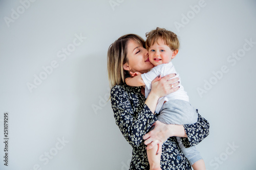 Mother and son on a white wall background at home