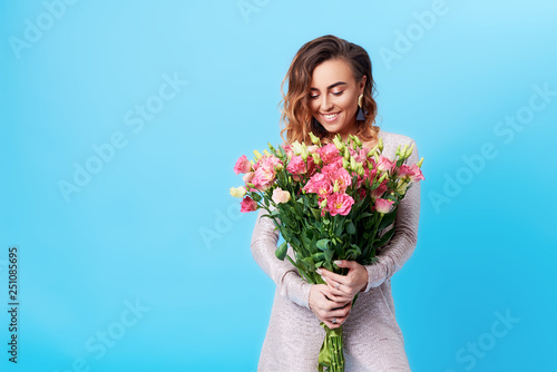 Young happy smiling redhead woman holding bouquet of colorful spring flowers isolated on blue background. Pink roses, festive bouquet in honor of women's day on March 8 or birthday © shcherban