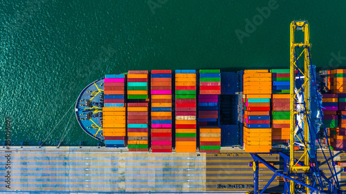 Leinwandbild Motiv Container cargo freight ship with working crane bridge discharge at container terminal, Aerial top view container ship at deep sea port.