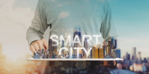 Smart city technology, a man using digital tablet, and modern buildings hologram © SasinParaksa