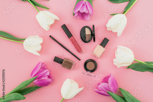 Leinwanddruck Bild Beauty composition with tulips flowers and cosmetics on pink background. Top view. Flat lay.