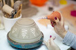 Clay pot in making proces by pottery artist with woman hands on  plan
