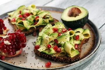 sliced avocado and ripe pomegranates on toast bread with spices and avocado.