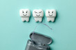 Leinwanddruck Bild - Healthy white teeth are smiling on green mint background and floss.