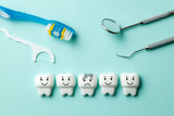 Healthy white teeth are smiling and tooth with caries is sad on green mint background. Toothbrush and dentist tools mirror, hook.
