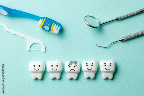 obraz PCV Healthy white teeth are smiling and tooth with caries is sad on green mint background. Toothbrush and dentist tools mirror, hook.
