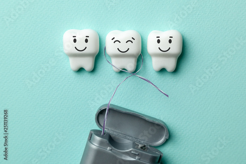 Leinwanddruck Bild Healthy white teeth are smiling on green mint background and floss.