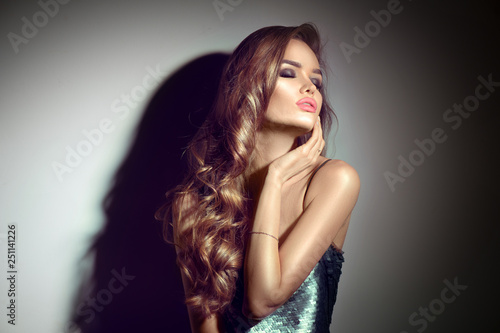 Leinwandbild Motiv Sexy young woman portrait. Seductive brunette girl posing in darkness. Beauty glamour lady with long curly hair in spotlight