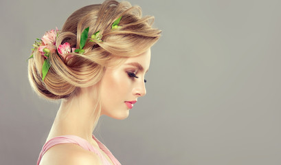 Beautiful model girl  with elegant hairstyle and rose flowers in a plait . Woman with fashion  spring hair. © Sofia Zhuravetc